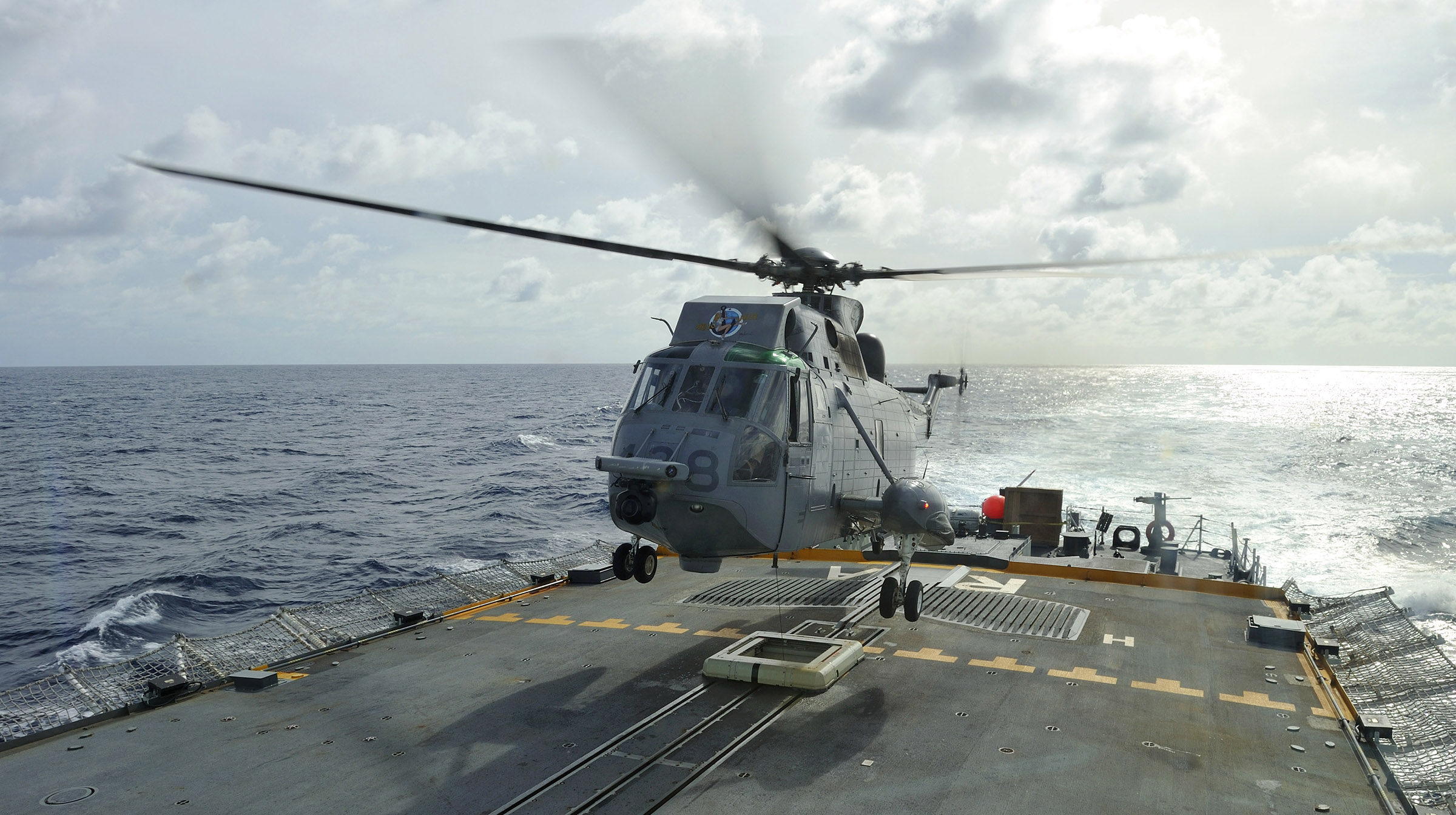 A large helicopter hovers a metre or two above the flight deck of a ship.