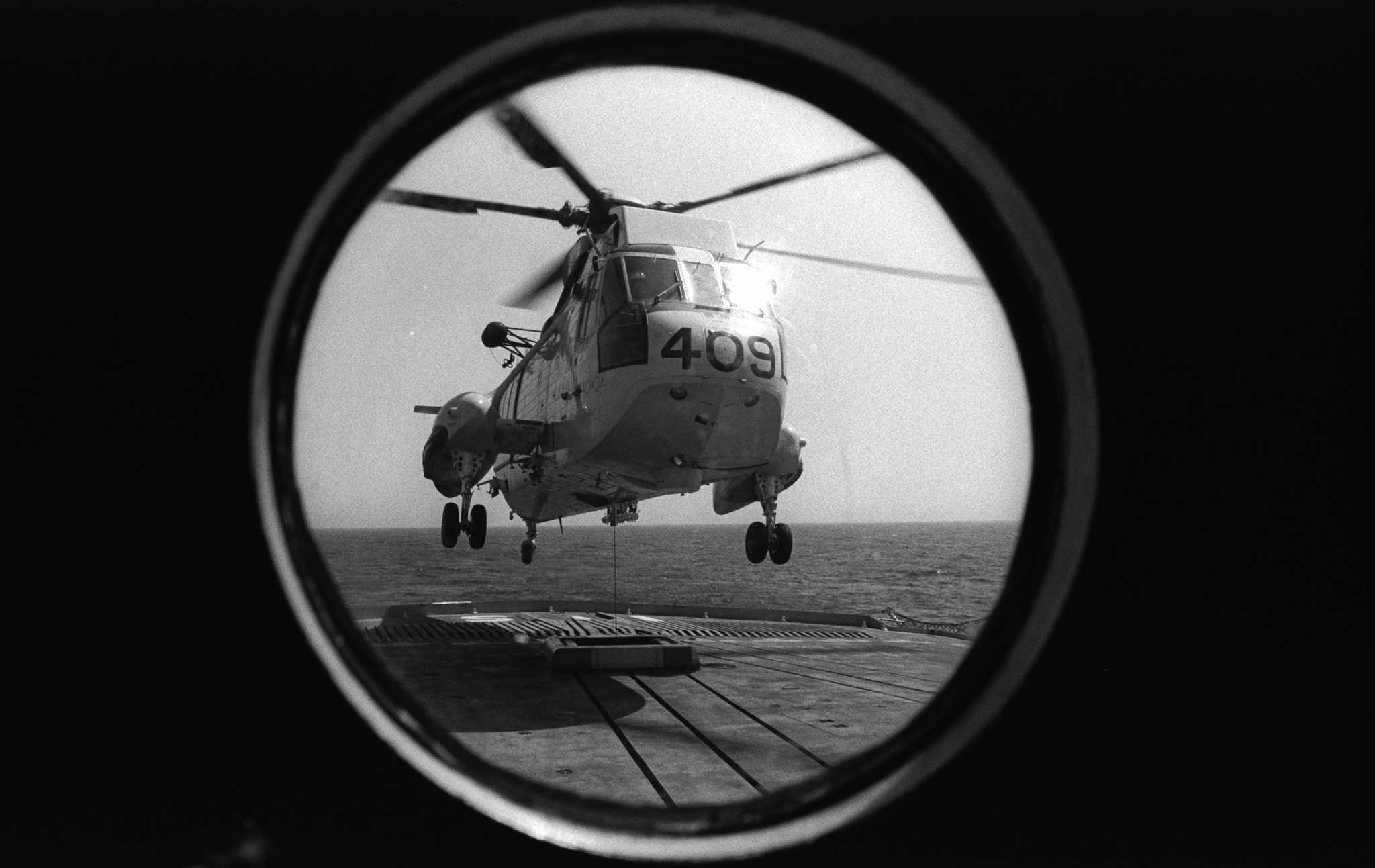 "A Sea King helicopter lands on the flight deck of Her Majesty's Canadian Ship Iroquois using a ""Beartrap"", circa 1976. PHOTO: DND Archives, IH76-111"