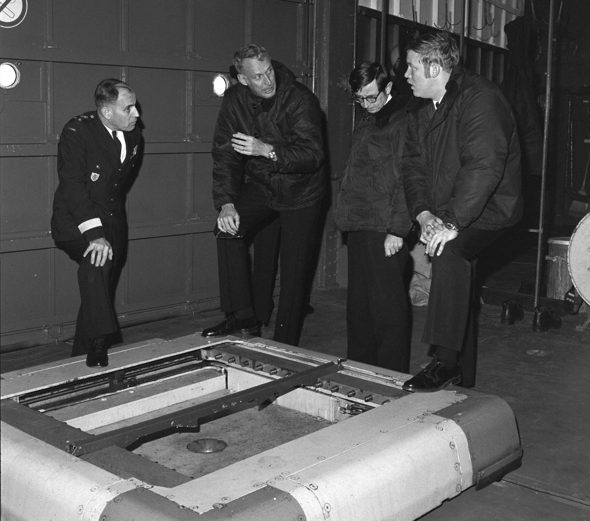 "Vice-Admiral John Boyle (left) discusses the ""Beartrap"" with United States Navy officers in an aircraft hangar, circa 1976. PHOTO: DND Archives, IH76-261"