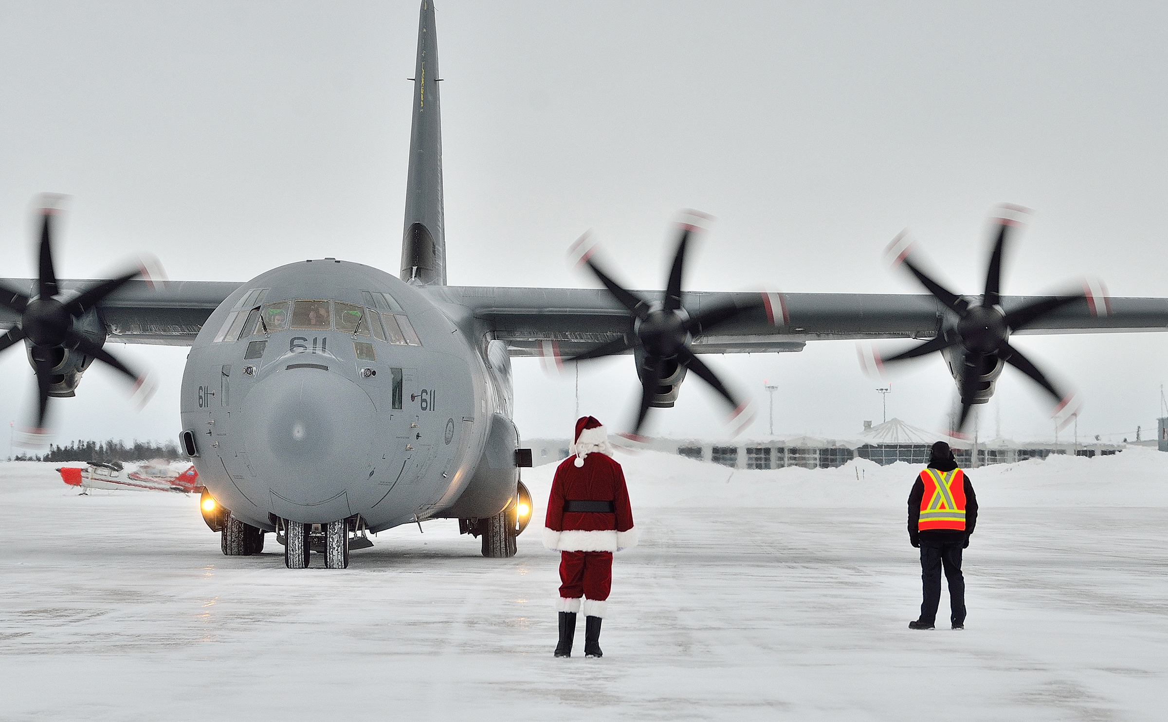 "Santa Claus and a member of the groundcrew wait to greet the aircrew on board a CC-130J Hercules aircraft from 8 Wing Trenton, Ontario, as it lands at 5 Wing Goose Bay Newfoundland and Labrador, on December 10, 2018. The transport aircraft was carrying toys for children in Canada's most isolated northern communities as part of the RCMP's annual ""Toys for the North"" campaign. PHOTO: Master Corporal Krista Blizzard, GB2018-12-040"