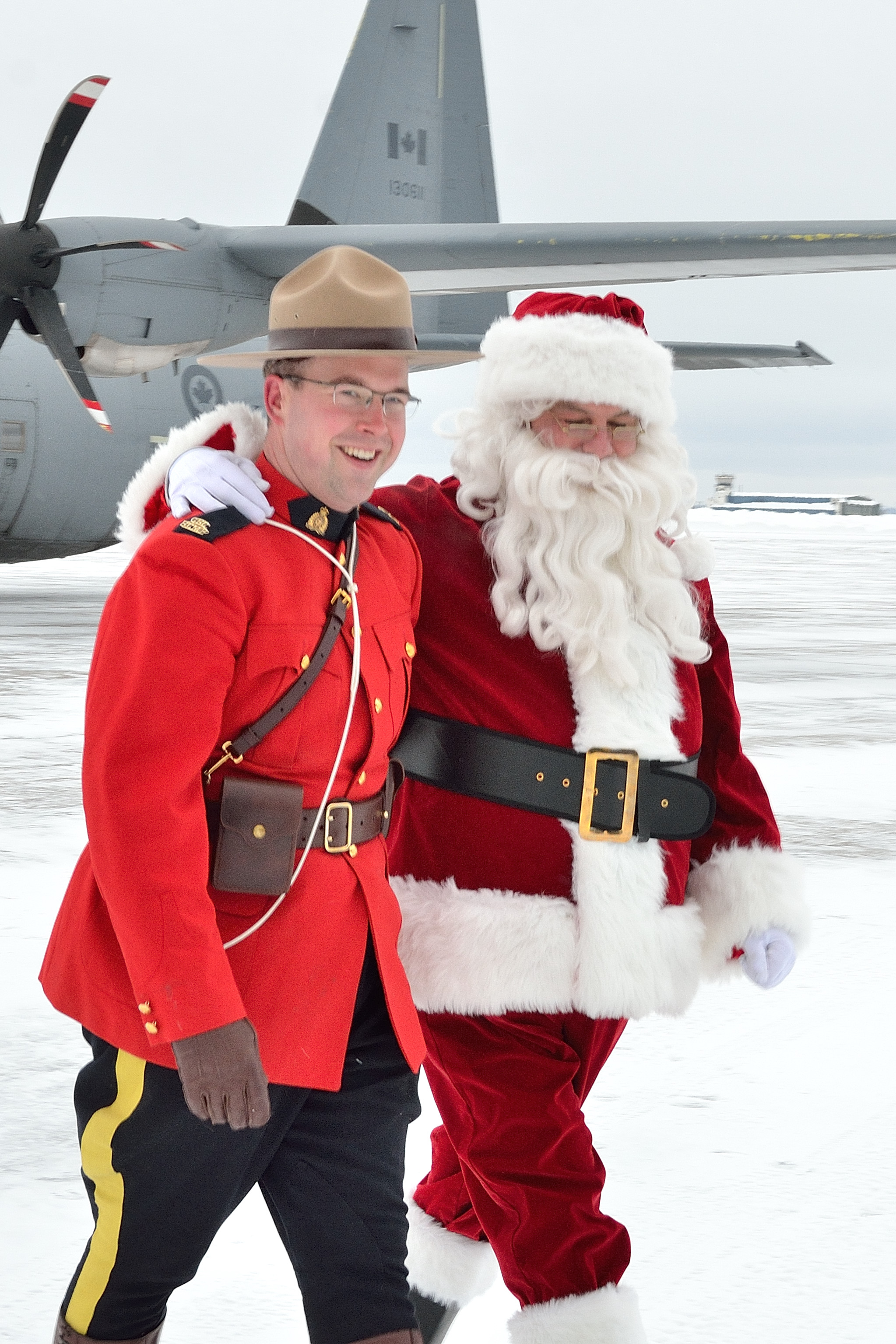 "Santa arrived at 5 Wing Goose Bay, Newfoundland and Labrador, on December 10, 2018, to oversee operations of the RCMP's annual ""Toys for the North"" campaign where toys are collected and distributed to children in Canada's most isolated Northern Communities. Constable Chris Attewell of the Happy Valley-Goose Bay RCMP Detachment and Santa are in good spirits as they walk across the tarmac together. PHOTO: Master Corporal Krista Blizzard, GB2018-12-049"