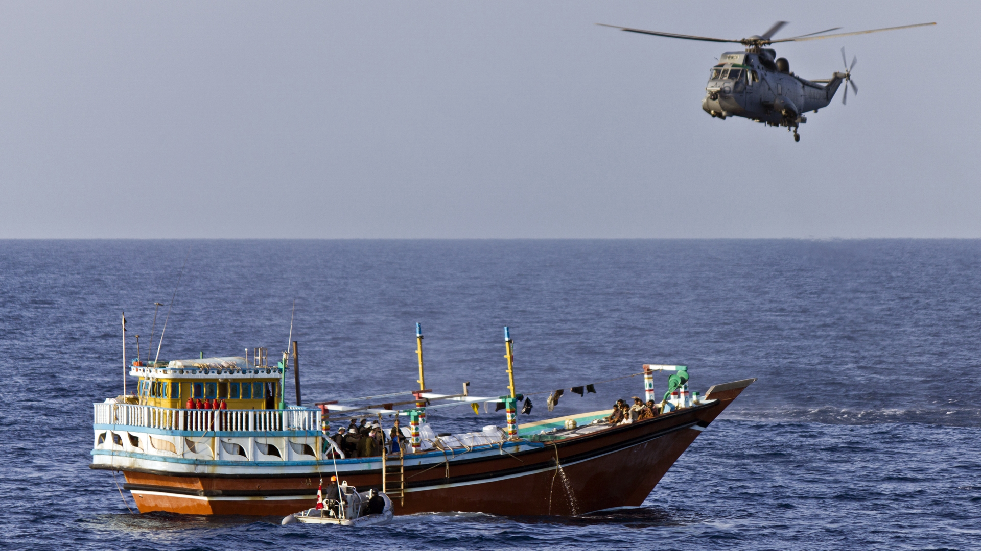 A Sea King provides cover as a boarding party from HMCS Charlottetown searches a dhow in the Gulf of Aden during Operation Artemis on May 5, 2012. PHOTO: Lieutenant (Navy) Darren Puttock, HS2012-0071-562