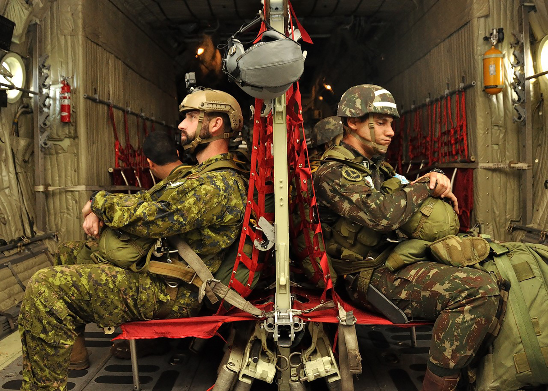 Onboard a Brazilian Air Force C-130, on November 20, 2018, Sergeant Alex Bossinotte (left), a jumpmaster from the Canadian Army Advanced Warfare Centre at CFB Trenton, and 1st Lieutenant Yuri Tavares (right) of the Brazilian Army Parachutist Instruction Center, take part in an airborne exercise during CRUZEX 2018, the key South American exercise that brings together militaries from eight allied and partner nations to conduct a wide range of training. PHOTO: Submitted