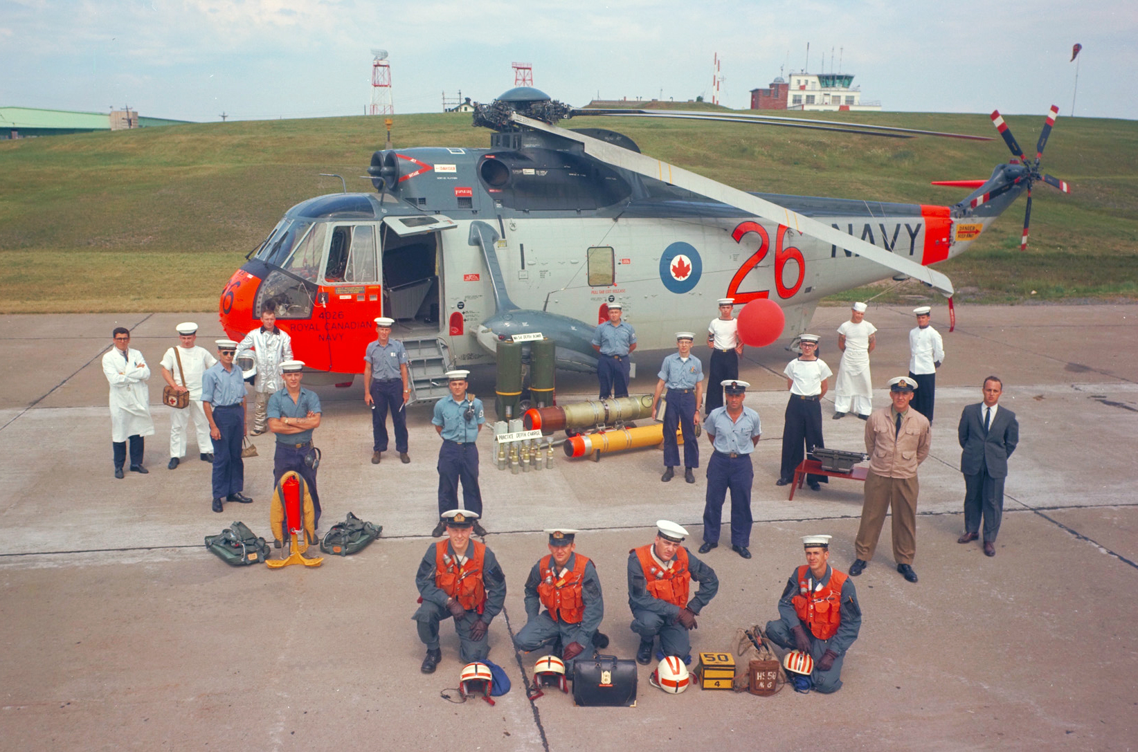 Representatives of all those who keep the Royal Canadian Navy's Sea King helicopters flying pose with the helicopter circa 1966. Among the occupations represented are maintenance, safety, aviation engineering, weapons, medical and administration. The helicopter is from HS-50 Squadron, based at Shearwater, Nova Scotia. PHOTO: DND Archives, SWC66-719-1