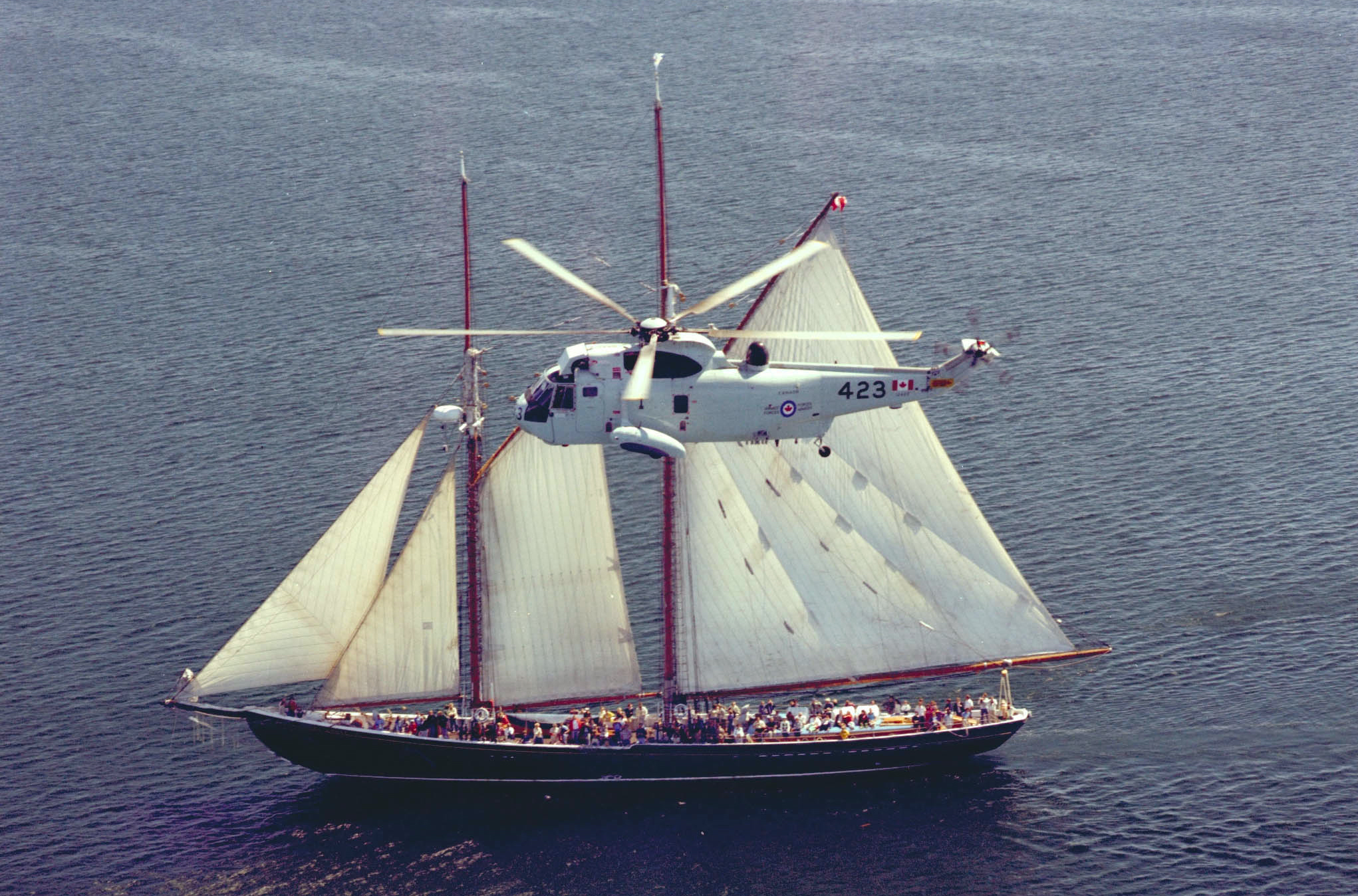 A Sea King flies near the Bluenose II on the East Coast, circa 1978. PHOTO: DND Archives, SWC78-1652