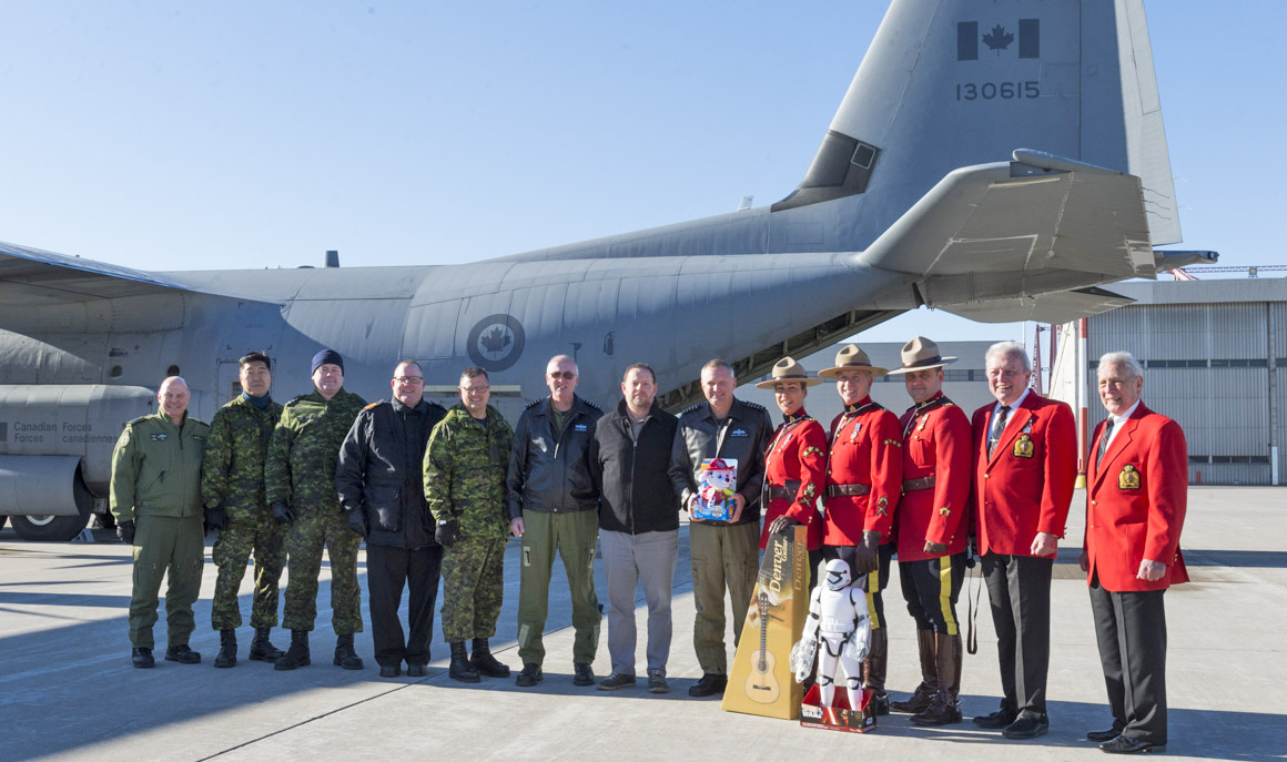 Members of the Royal Canadian Mounted Police and Royal Canadian Air Force combined forces to bring toys to remote northern communities in Canada. They gathered for a photo before departing from 8 Wing Trenton, Ontario, on December 7, 2018. PHOTO: Leading Seaman Dan Bard, TN09-2018-0436-012