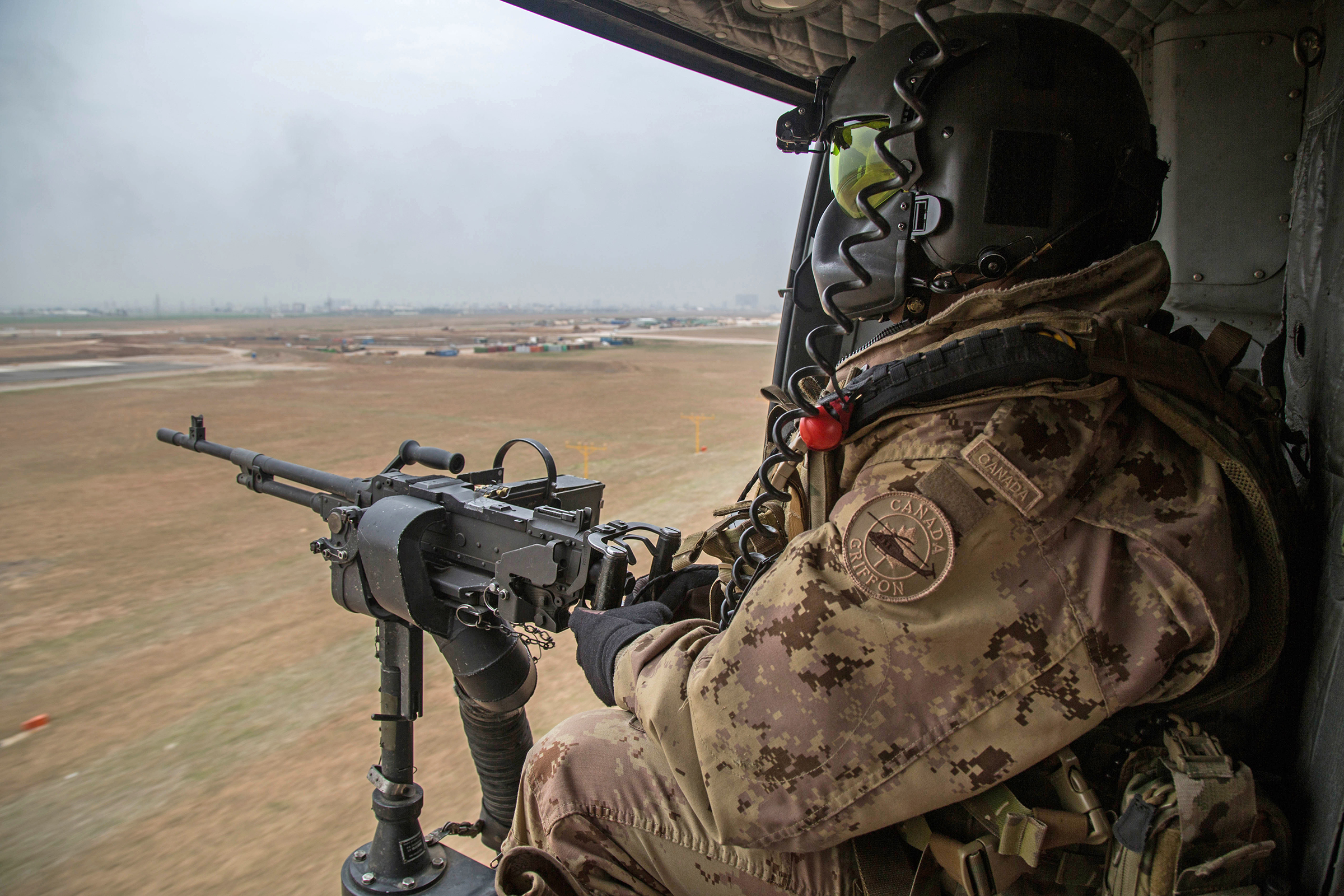 A tactical aviation door gunner keeps watch during a CH-146 Griffon helicopter flight near Erbil, Iraq, on March 2, 2017, during Operation Impact. PHOTO: Courtesy, U.S. Combat Camera, 170302-JA380-A-002
