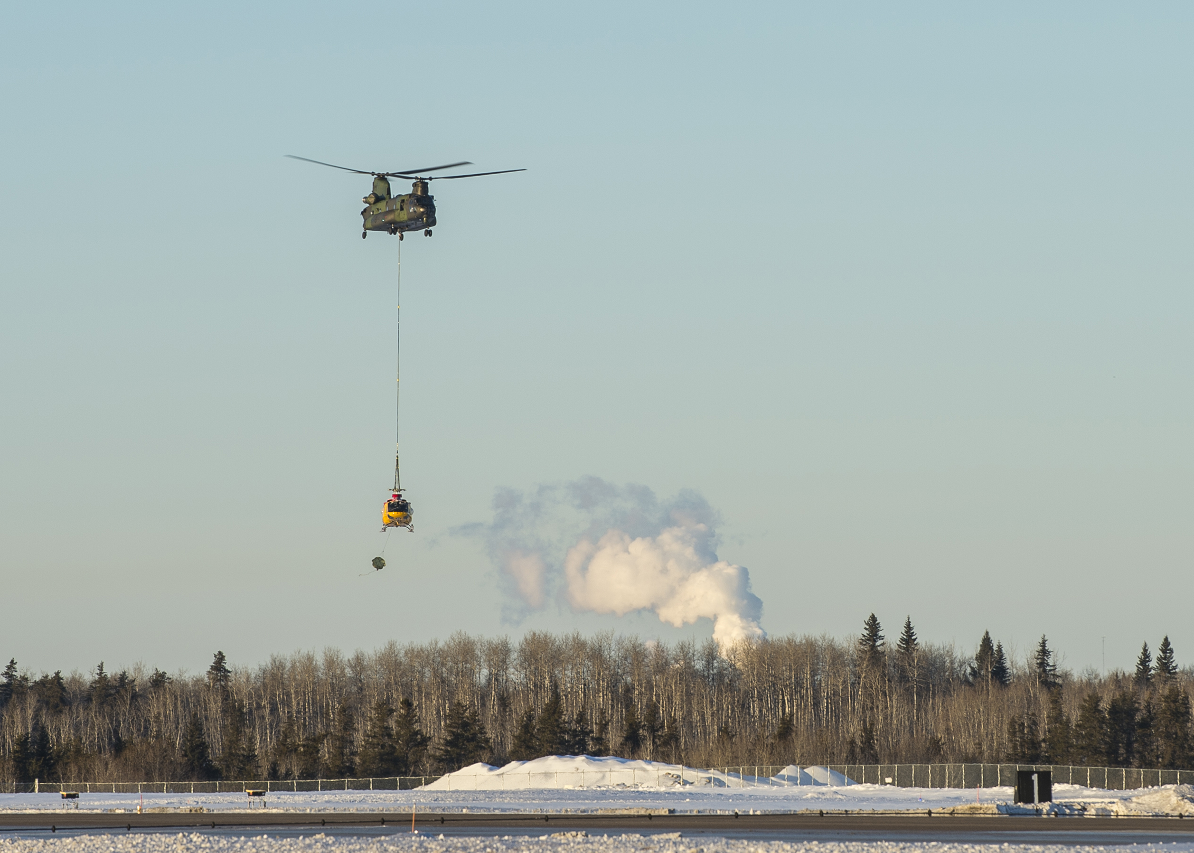 A CH-147F Chinook helicopter from 450 Tactical Helicopter Squadron, located in Petawawa, Ontario, approaches the 4 Wing Cold Lake, Alberta, airfield on January 15, 2019, to deliver a damaged CH-146 Griffon helicopter that it had transported from a remote area in the Cold Lake Air Weapons Range. PHOTO: Able Seaman Mathieu Potvin, AE02-2019-0011-007