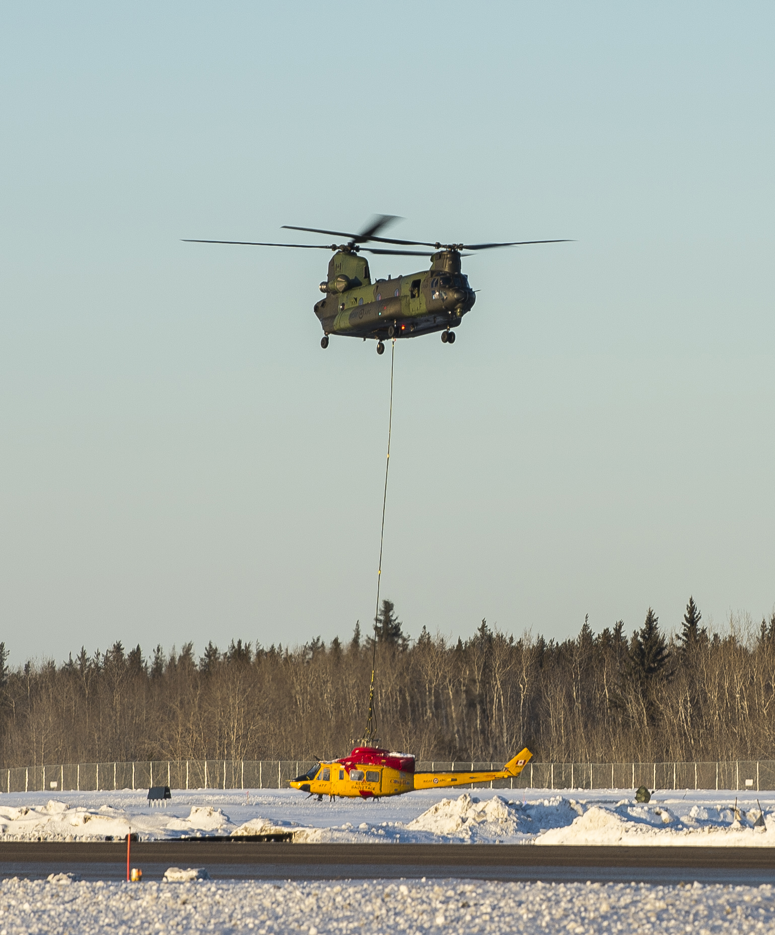 Almost there! The Chinook helicopter lowers the damaged Griffon beside the runway at 4 Wing Cold Lake after transporting it from a remote area of the Cold Lake Air Weapons Range. PHOTO: Able Seaman Mathieu Potvin, AE02-2019-0011-008