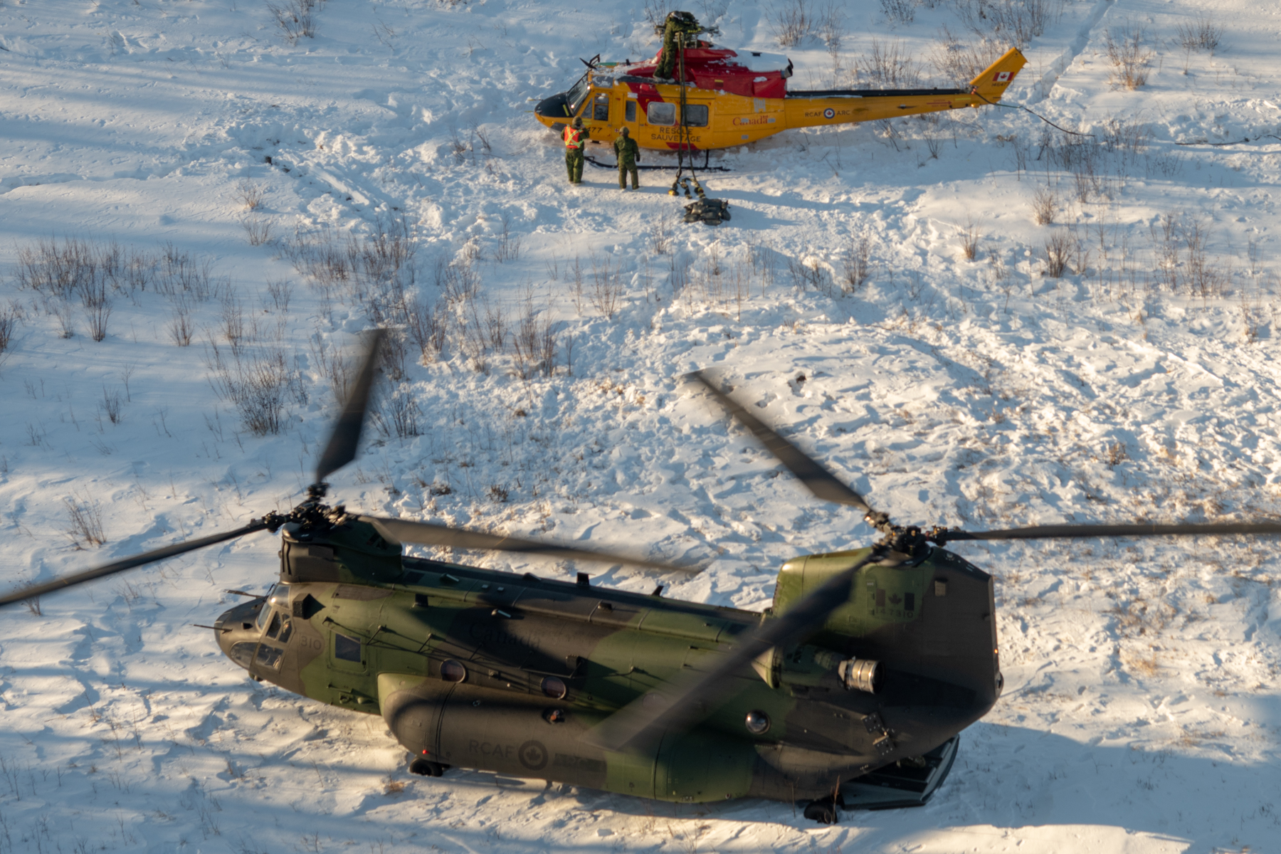 A CH-147F Chinook helicopter rests on the snow in the Cold Lake Air Weapons Range near a damaged CH-146 Griffon helicopter. Slings are being attached to the Griffon, which has had equipment such as its blades and tail rotor removed, in preparation for the Chinook airlifting it back to 4 Wing. PHOTO: Master Corporal Amy Martin, AE05-2019-0007-025