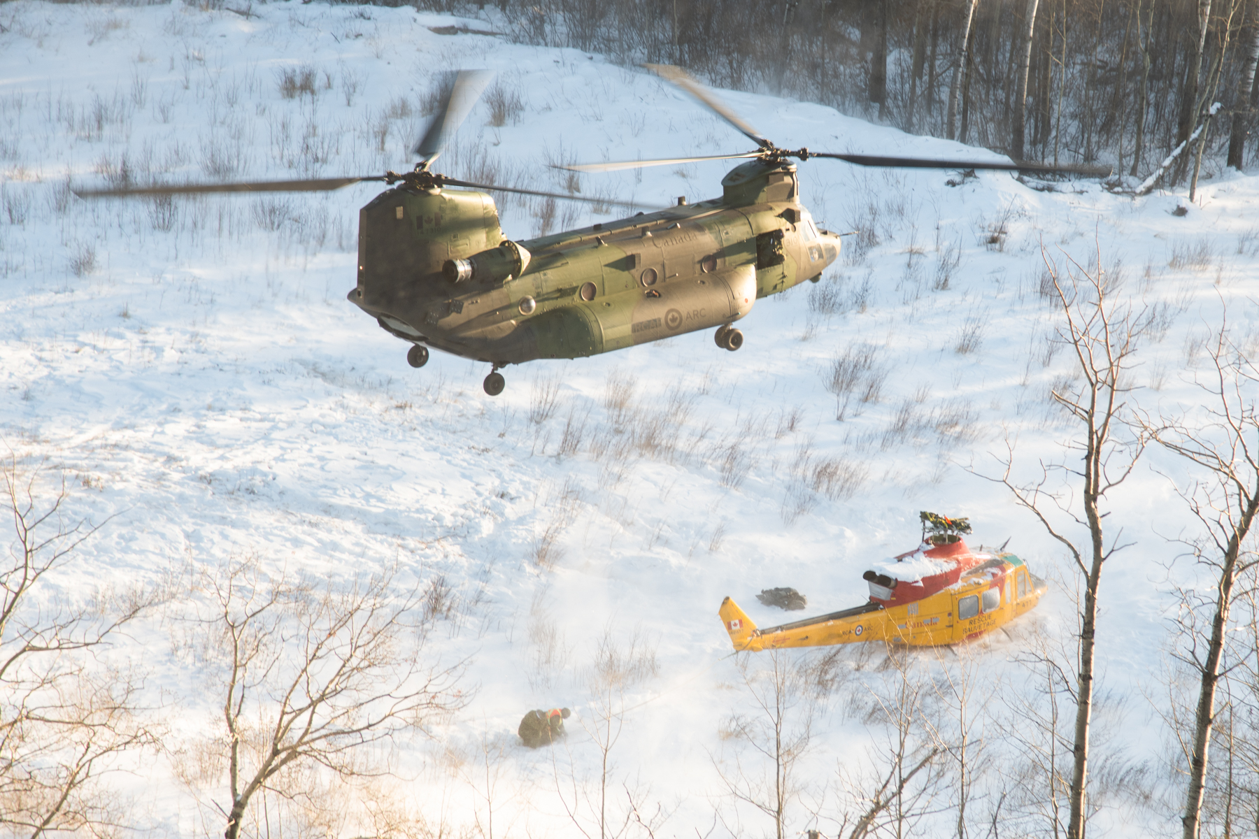 The Chinook helicopter prepares to lift the damaged Griffon off the ground. Behind the Griffon, military personnel hold a drogue parachute, attached to the Griffon's tail, steady in the downdraft from the Chinook's blades. PHOTO: Master Corporal Amy Martin, AE05-2019-0007-030