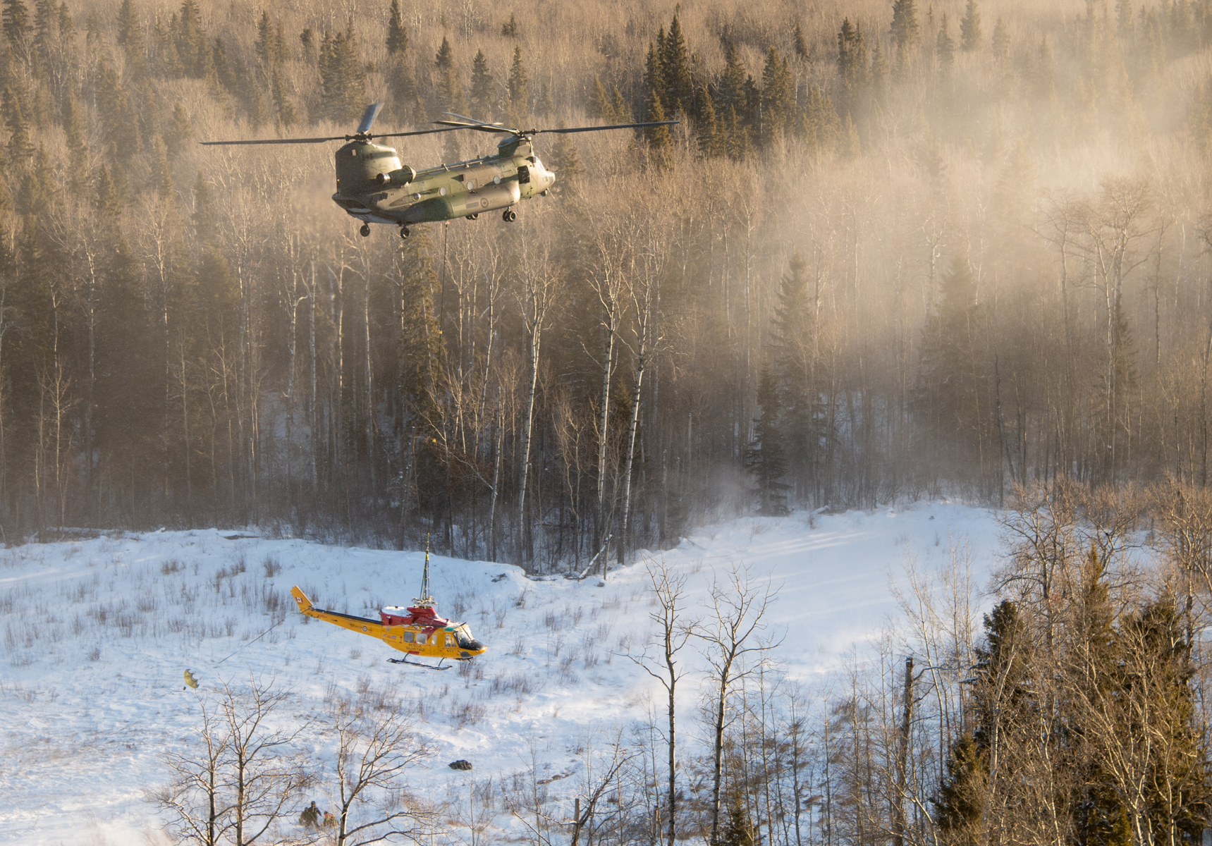 The Chinook helicopter lifts off with the Griffon slung below it. Note that the Griffon is not yet aligned with the Chinook and the drogue chute has not fully filled with air to steady the smaller helicopter. PHOTO: Master Corporal Amy Martin, AE05-2019-0007-039