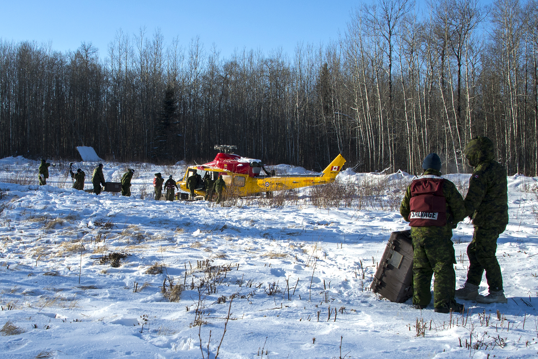 Members of 4 Wing Cold Lake's recovery and salvage team remove parts from a CH-146 Griffon that had an emergency landing in the Cold Lake Air Weapons Range in December 2018. They were preparing the Griffon for lift and recovery back to 4 Wing by a CH-147F Chinook helicopter from 450 Tactical Helicopter Squadron on January 15, 2019. PHOTO: Master Corporal Raulley Parks, AE09-2019-0011-0011