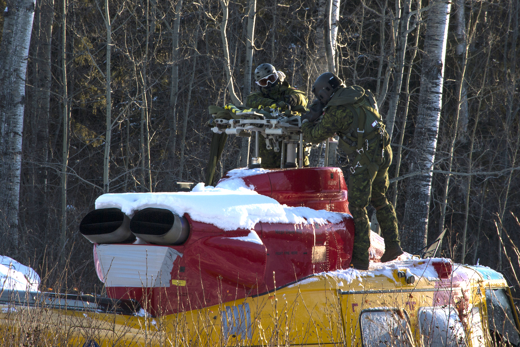 A loadmaster and another individual from 450 Tactical Helicopter Squadron, based in  Petawawa, Ontario, inspects the sling rigging on a damaged CH-146 Griffon helicopter in preparation for its lift and recovery from a remote location in the Cold Lake Air Weapons Range back to 4 Wing Cold Lake, Alberta. PHOTO: Master Corporal Raulley Parks, AE09-2019-0011-0012