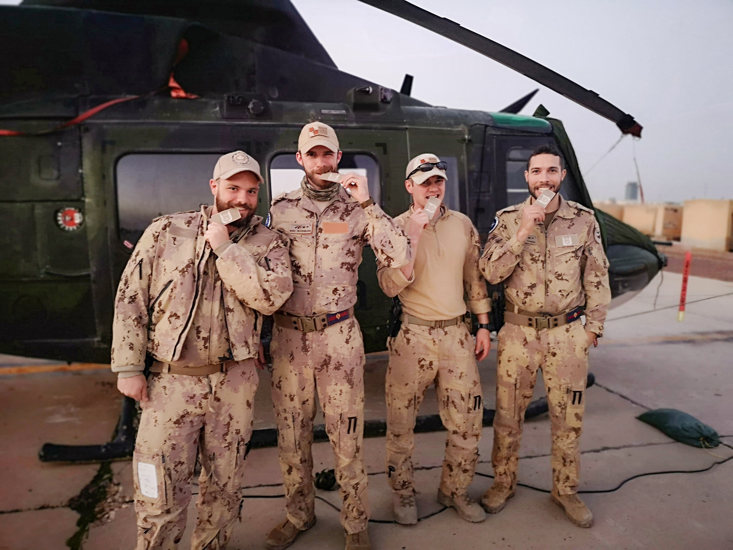 Four people wearing desert camouflage pattern uniforms stand in front of a helicopter and each bites the corner of a small embroidered piece of cloth.