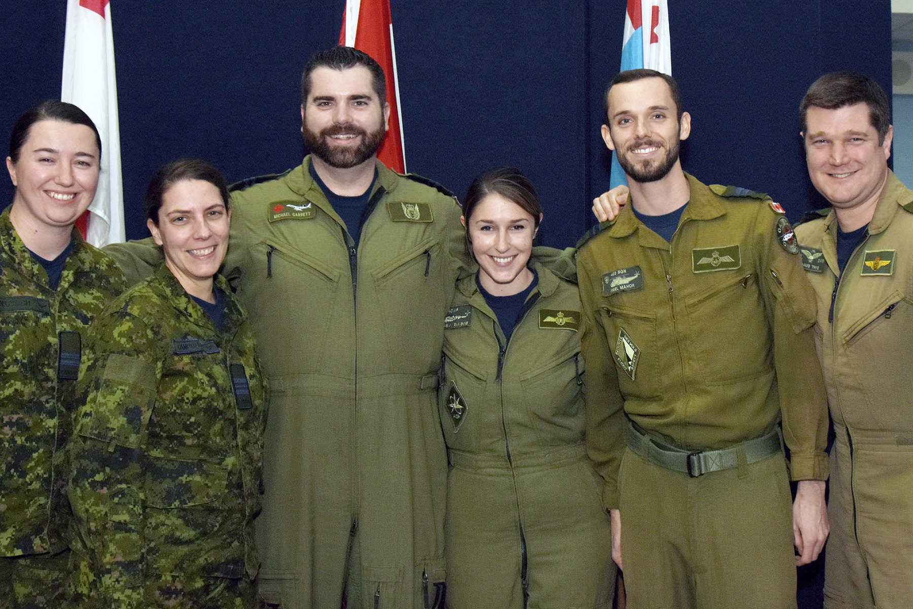 Six people wearing green military uniforms standing and smiling.