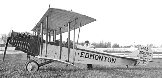 "An old biplane with the word ""Edmonton"" written on the side of the fuselage and ""May Airplanes Ltd. Edmonton"" written on the tail. One person sits in the cockpit and another stands behind the aircraft."