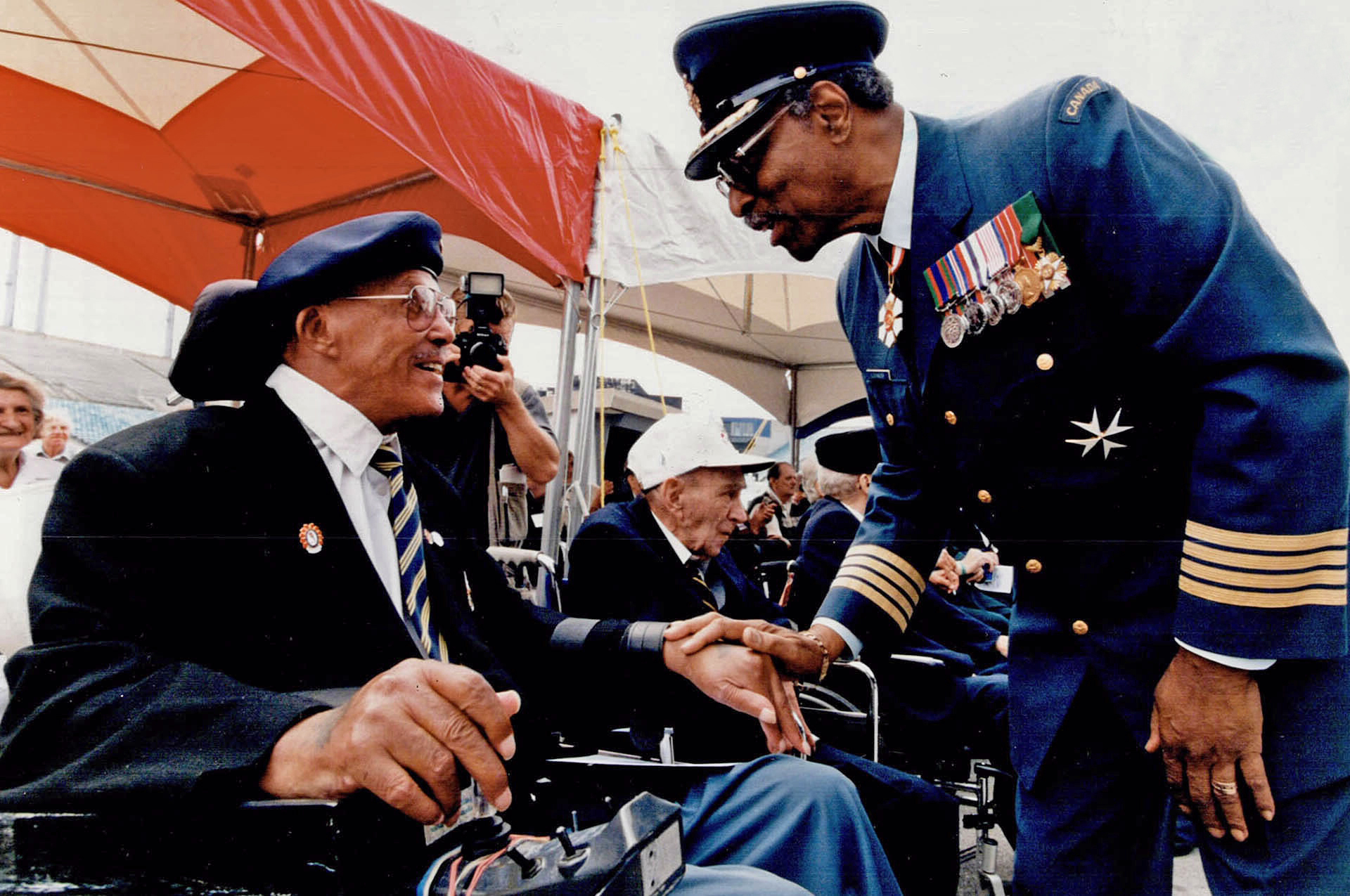 Lieutenant Governor Lincoln Alexander, wearing the uniform of an honorary colonel of the Air Force, speaks with a veteran. PHOTO: Toronto Star Archives, tspa_0028978f