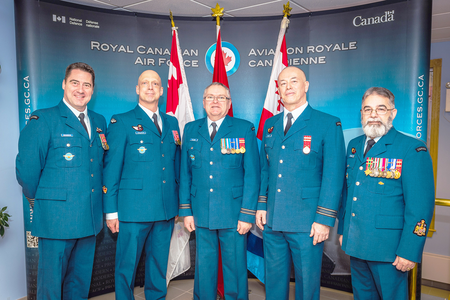 "Five men in blue uniforms with medals stand in a row in front of flags and a blue backdrop reading ""Royal Canadian Air Force 