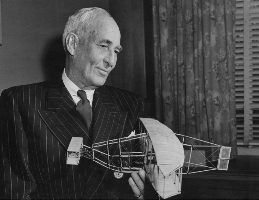 An older man wearing a suit holds a model of a very old airplane constructed mainly of wire and wooden struts.
