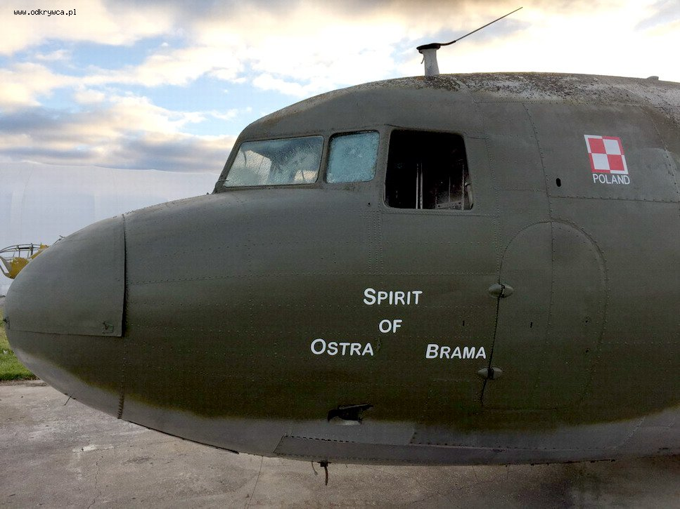 "A photo of the nose of an olive-green aircraft on which are painted the words ""Spirit of Ostra Brama""."