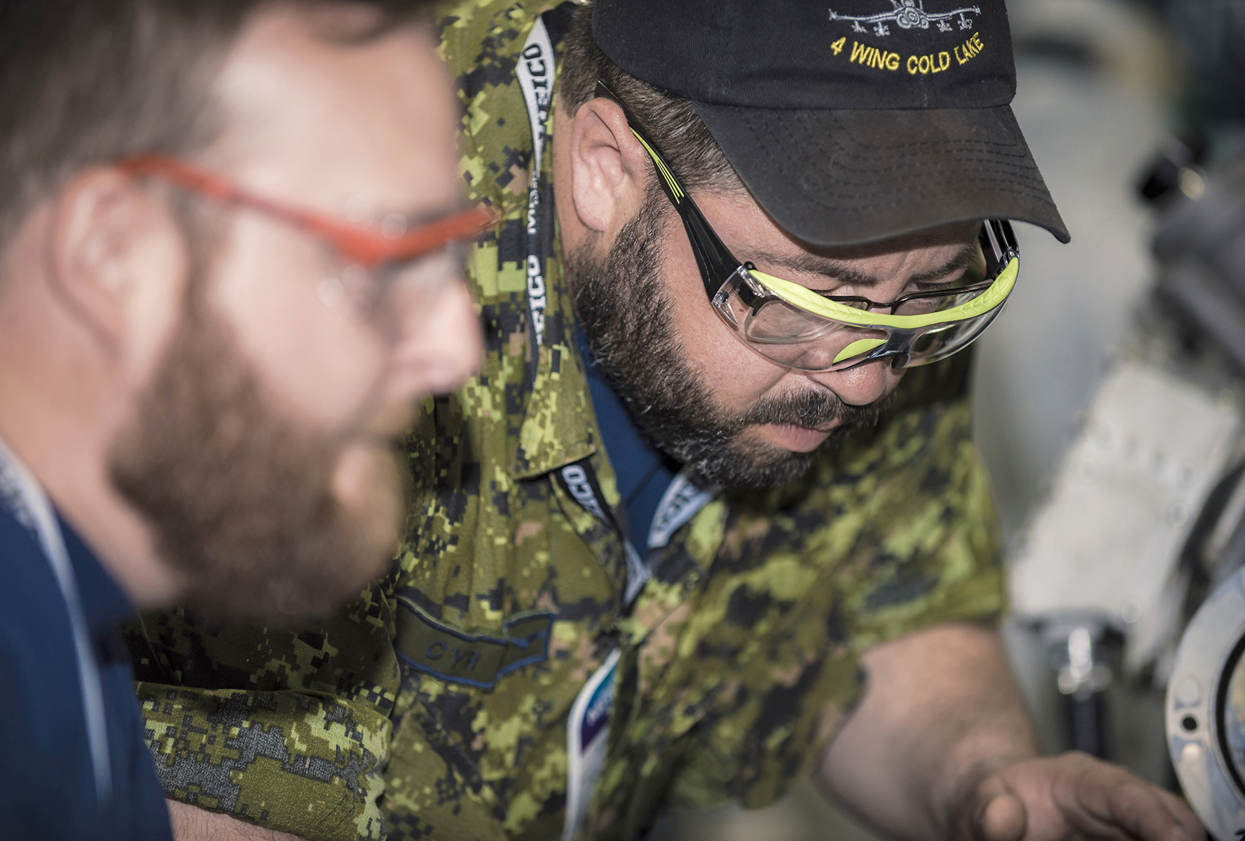 "Master Corporal Scott Gillian (left) and Sergeant Frank Cyr, both members of the 401 ""Rams"" Team, 4 Wing Cold Lake, perform an engine service task PHOTO: RCAF"