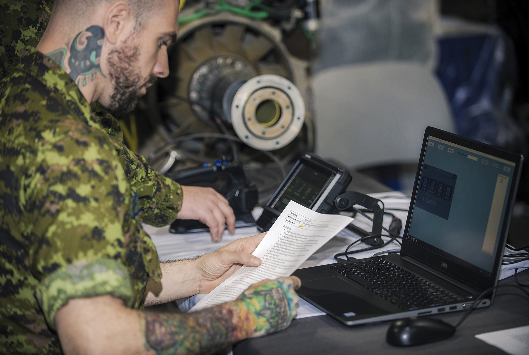 Corporal Marc-André Duguay, AVS, from 424 Transport and Rescue Squadron, Trenton and a member of the RCAF SAR Maintenance Team, reads the instructions for an engine service task. PHOTO: RCAF