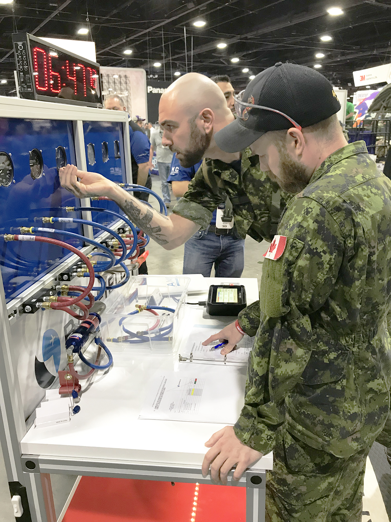 Master Corporal Simon Laurent (foreground), of 442 Transport and Rescue Squadron, guides Corporal Marc-André Duguay, AVS, from 424 Transport and Rescue Squadron, through a troubleshooting procedure during the Aerospace Maintenance Competition. Both were members of the RCAF SAR Maintenance Team. PHOTO: RCAF