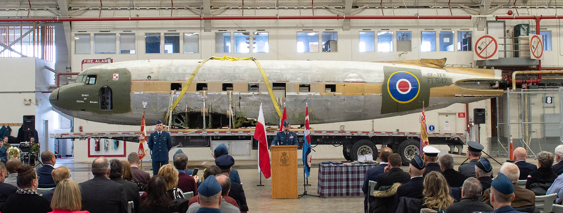 Inside a large building, a man stands at a lectern, addressing a group of seated people. Behind him is the fuselage of a large aircraft resting on a flatbed trailer.