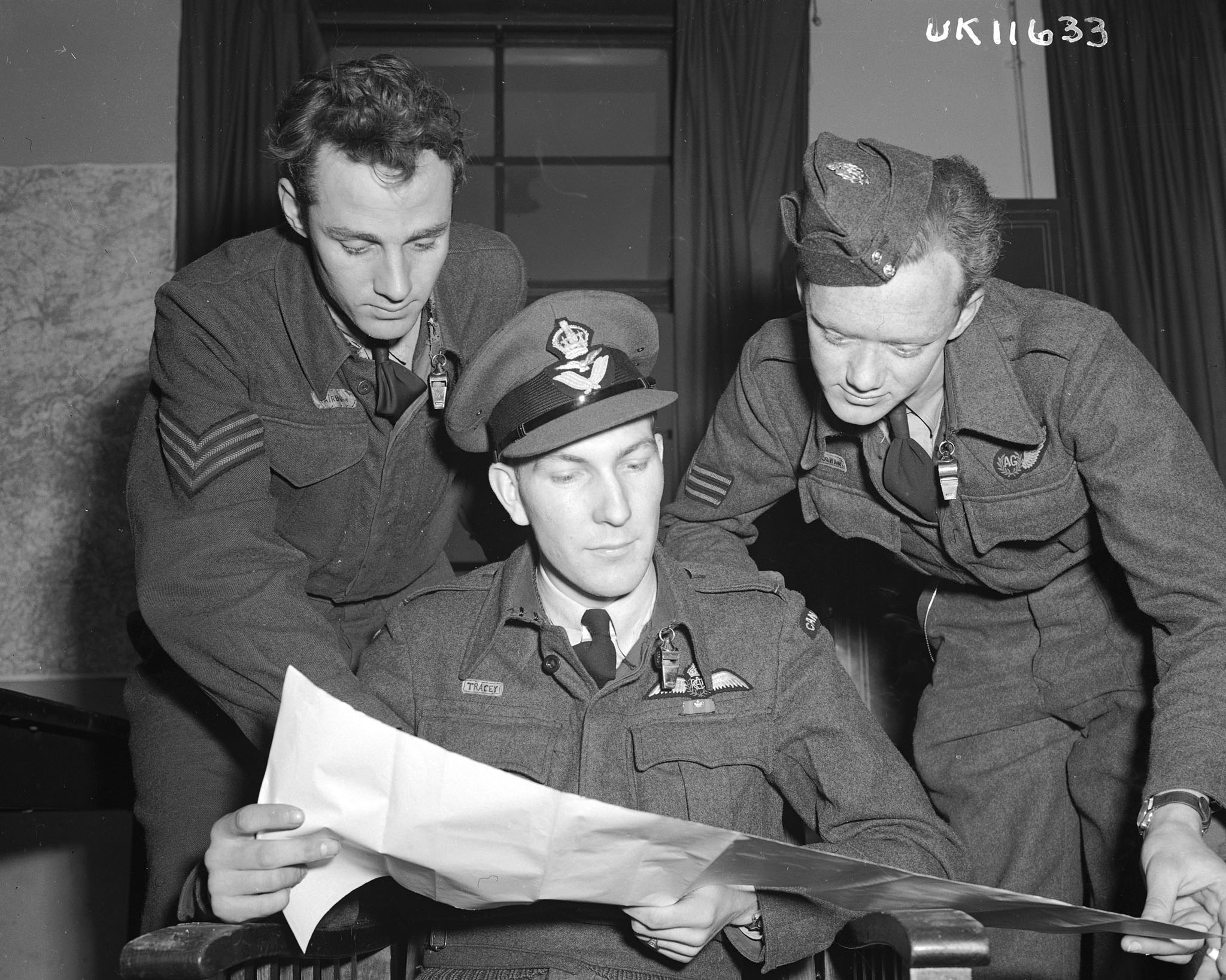 Three men wearing military uniforms look at a large sheet of paper.