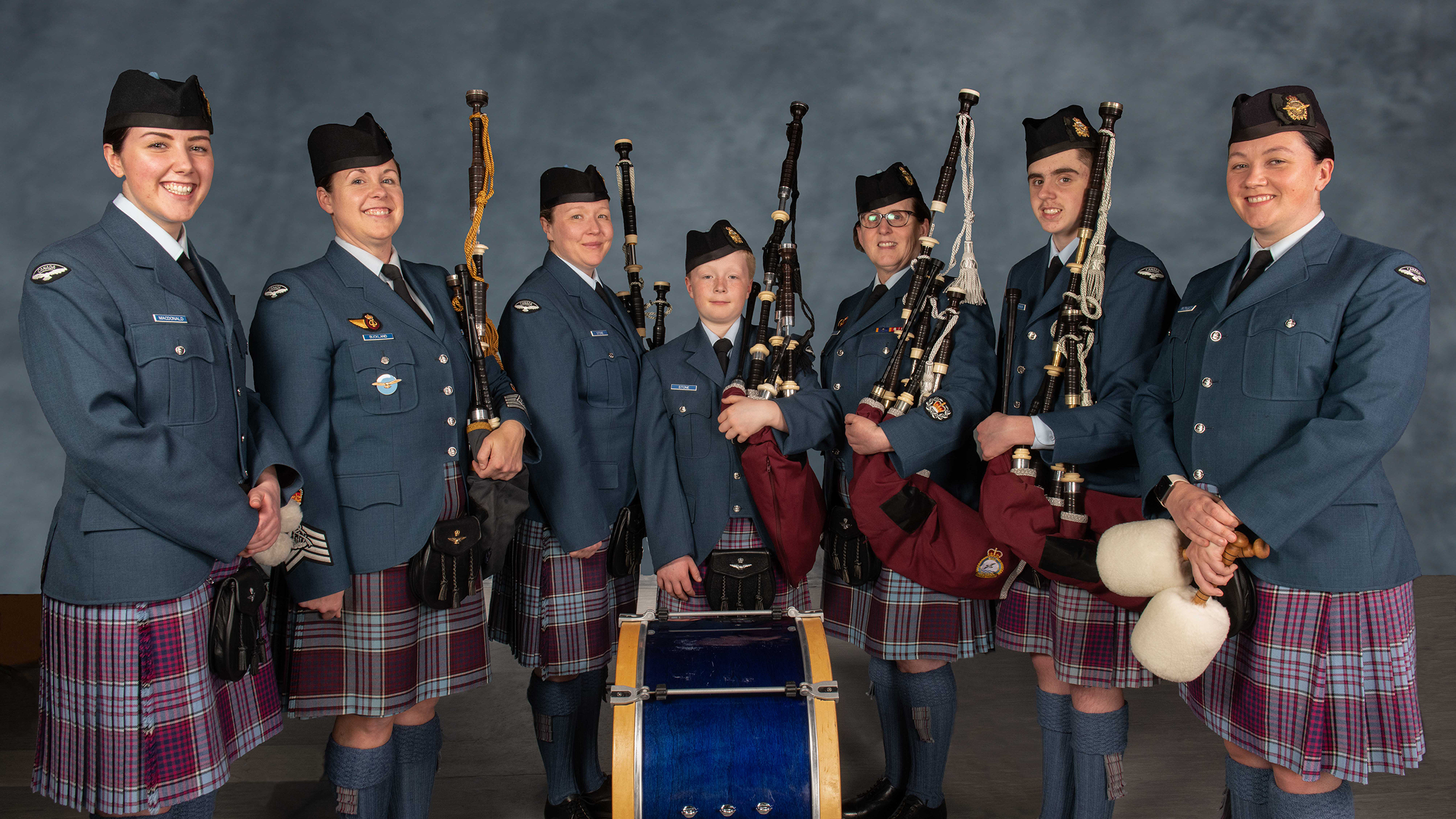 Seven people wearing military tunics and RCAF tartan kilts stand in a row behind a bass drum; five of them hold bagpipes.