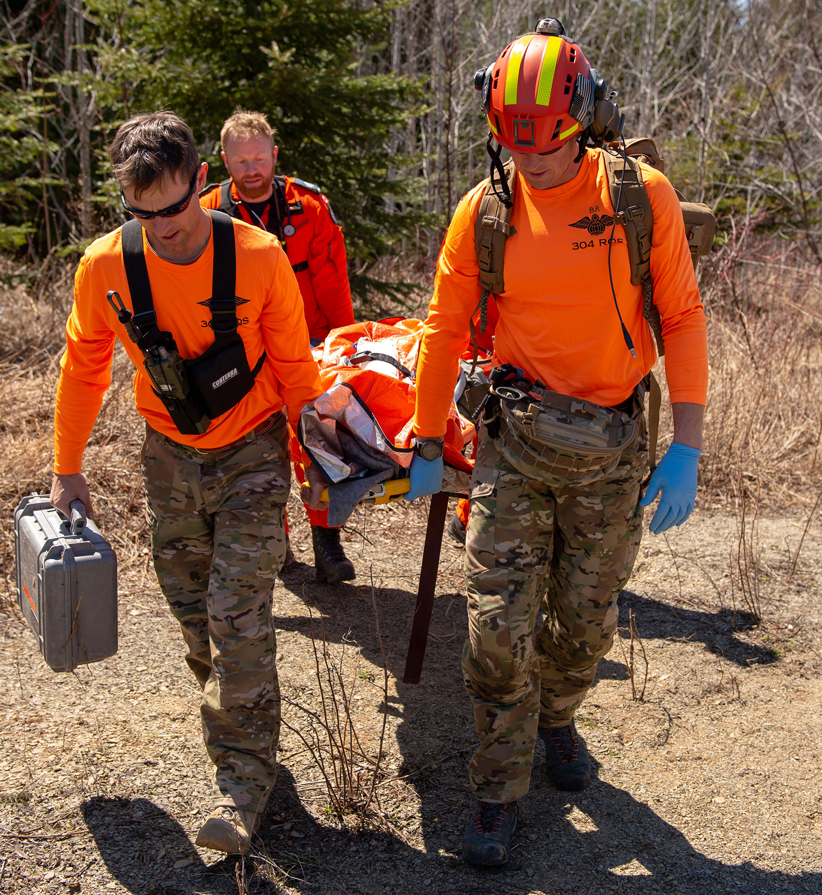 United States Air Force combat search and rescue para jumpers (foreground) and RCAF search and rescue technicians evacuate a simulated casualty on a litter on May 7, 2019, during Chinthex 2019, held near Thunder Bay, Ontario. PHOTO: Corporal Bryce Cooper, WG2019-0191-090