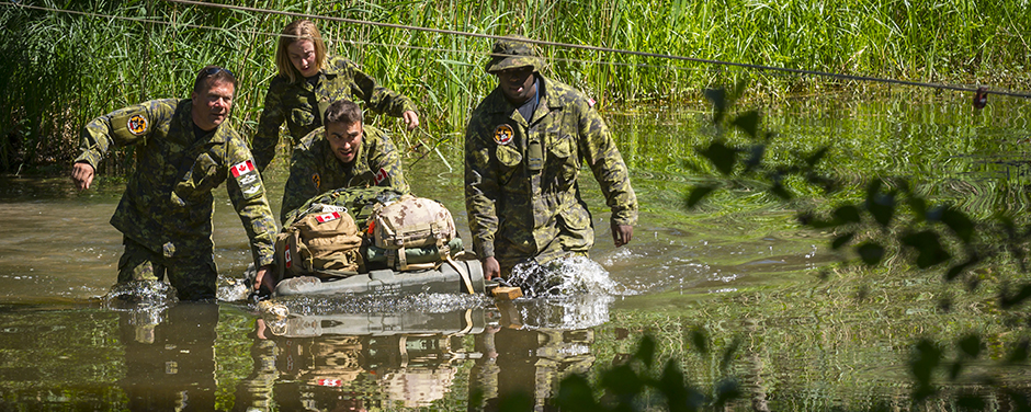 slide - Four people wearing military uniforms pull and push a small raft with backpacks on top of it through thigh-deep water