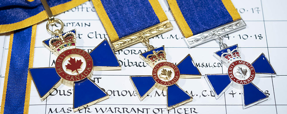 slide - Three medals on blue and gold ribbons, all of them comprising blue crosses with red-bordered circles in the centre and topped with crowns, are displayed on a chart inscribed with people's ranks and names.