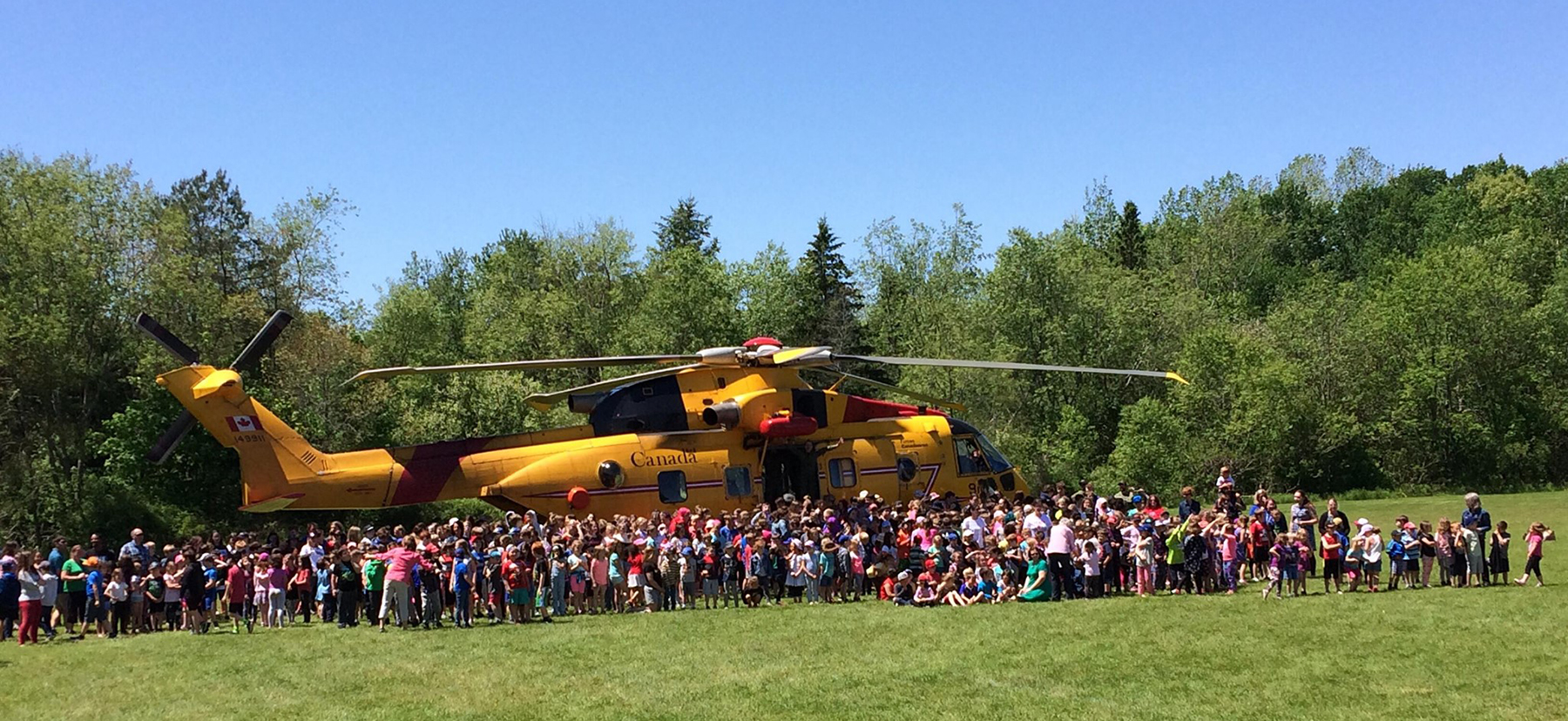 Under a clear blue sky, a very large group of children and a few adults gather in front of a large yellow helicopter sitting in a field, with trees in the background.