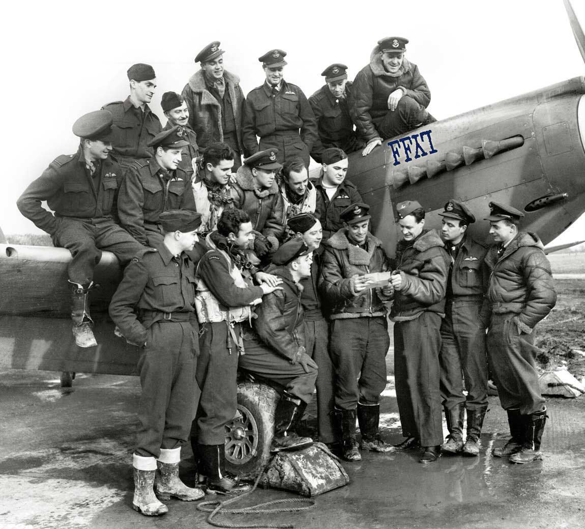 A group of men wearing military uniforms crouch on top of or stand in front of a single-propeller fighter aircraft, looking at a letter that two of the men are holding between them.