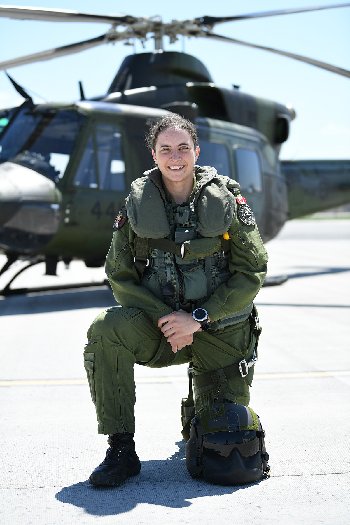 A smiling woman wearing a military flight suit bent on one knee on a runway. There is a military helicopter behind her.