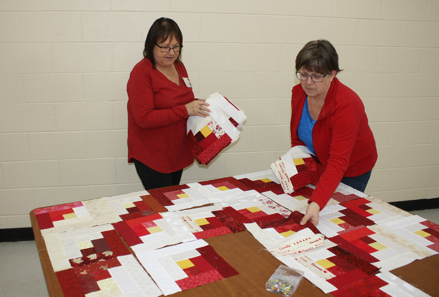 Brenda Hulan, left, and Mary Ewing lay out the pattern of colours and prints for the next Quilts of Valour project being assembled by a Greenwood-based group of program volunteers. PHOTO: Sara White