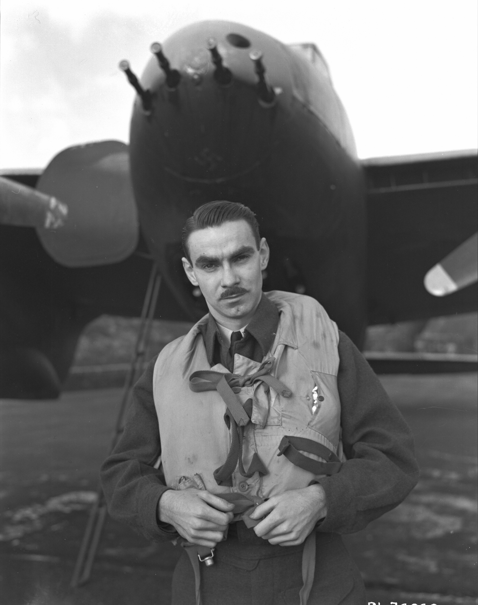 A black and white photo of a man wearing a military uniform, including a life jacket, standing in front of a propeller driven fighter aircraft.