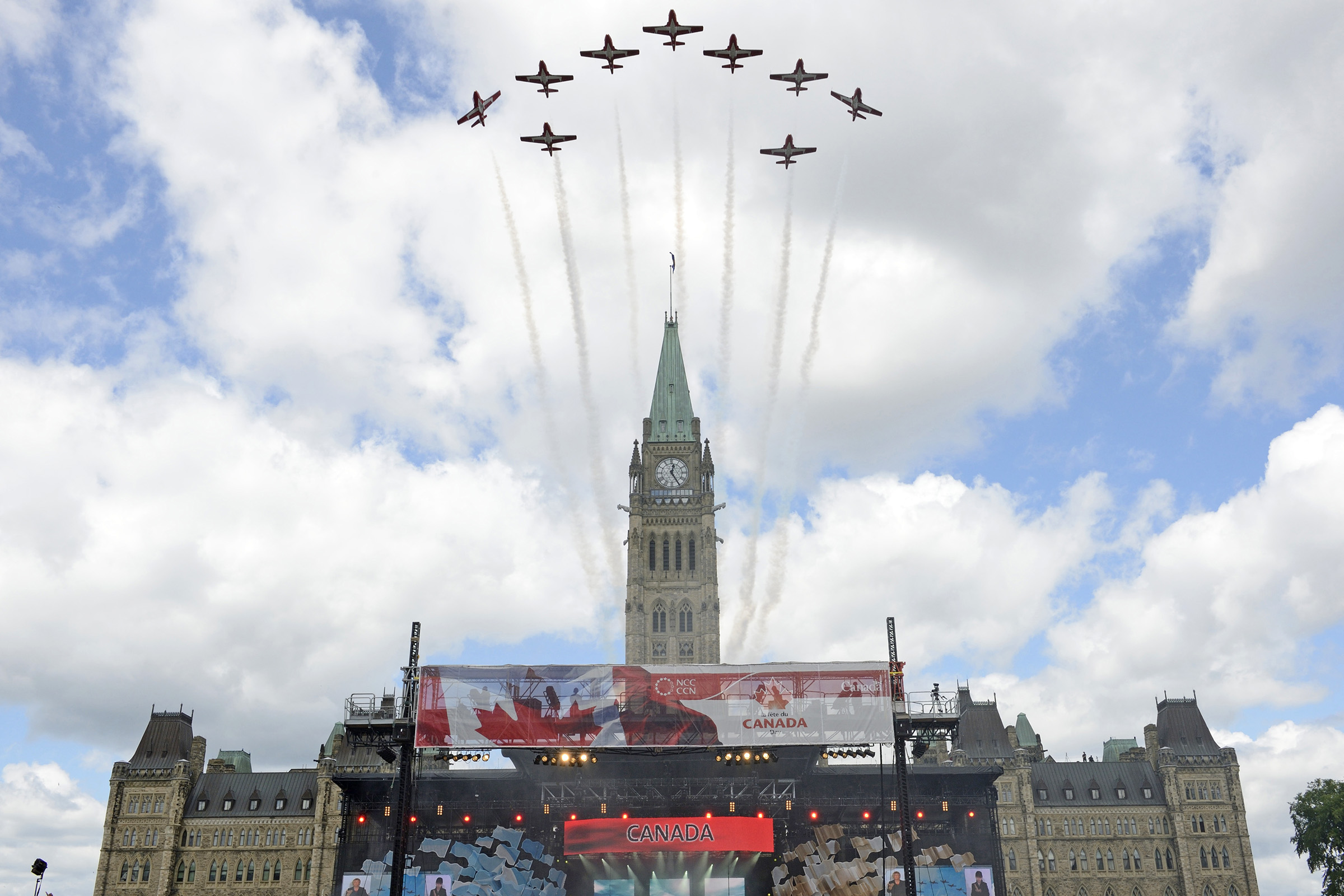 Several aircraft flying in a fan-shaped formation fly above the Peace Tower on Parliament Hill.