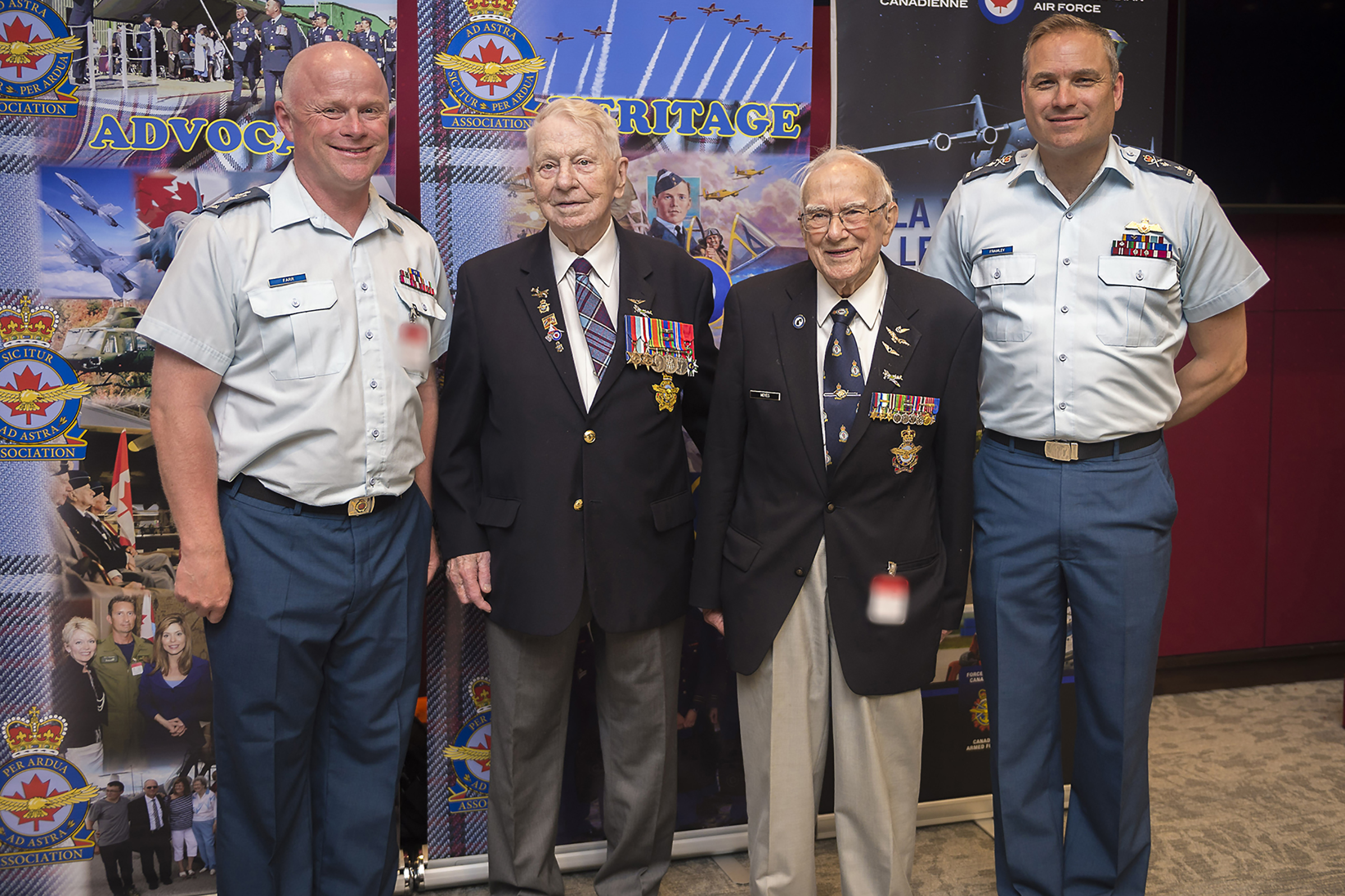 Two men in blue uniforms and two older men wearing dark blazers hung with medals stand in a row in front of display banners featuring aircraft, badges and people in uniform.