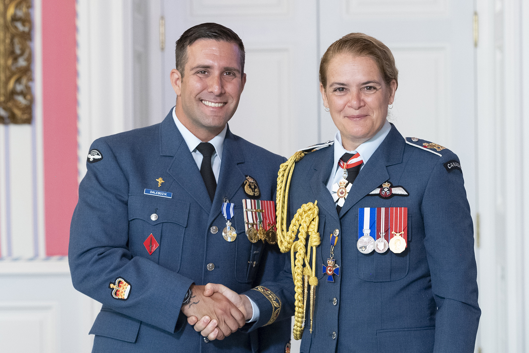 A woman and a man, both wearing blue military uniforms with medals, shake hands and smile.
