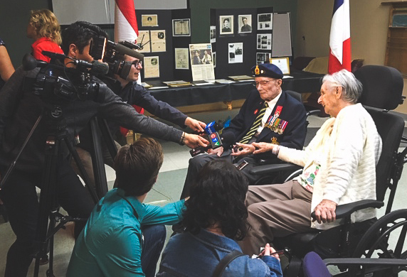 Reporters holding cameras and microphones lean towards an elderly couple who are both sitting in wheelchairs. The man wears a beret and a blazer with several military medals on it.
