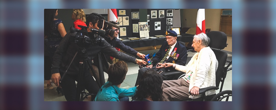 slide - Reporters holding cameras and microphones lean towards an elderly couple who are both sitting in wheelchairs. The man wears a beret and a blazer with several military medals on it.