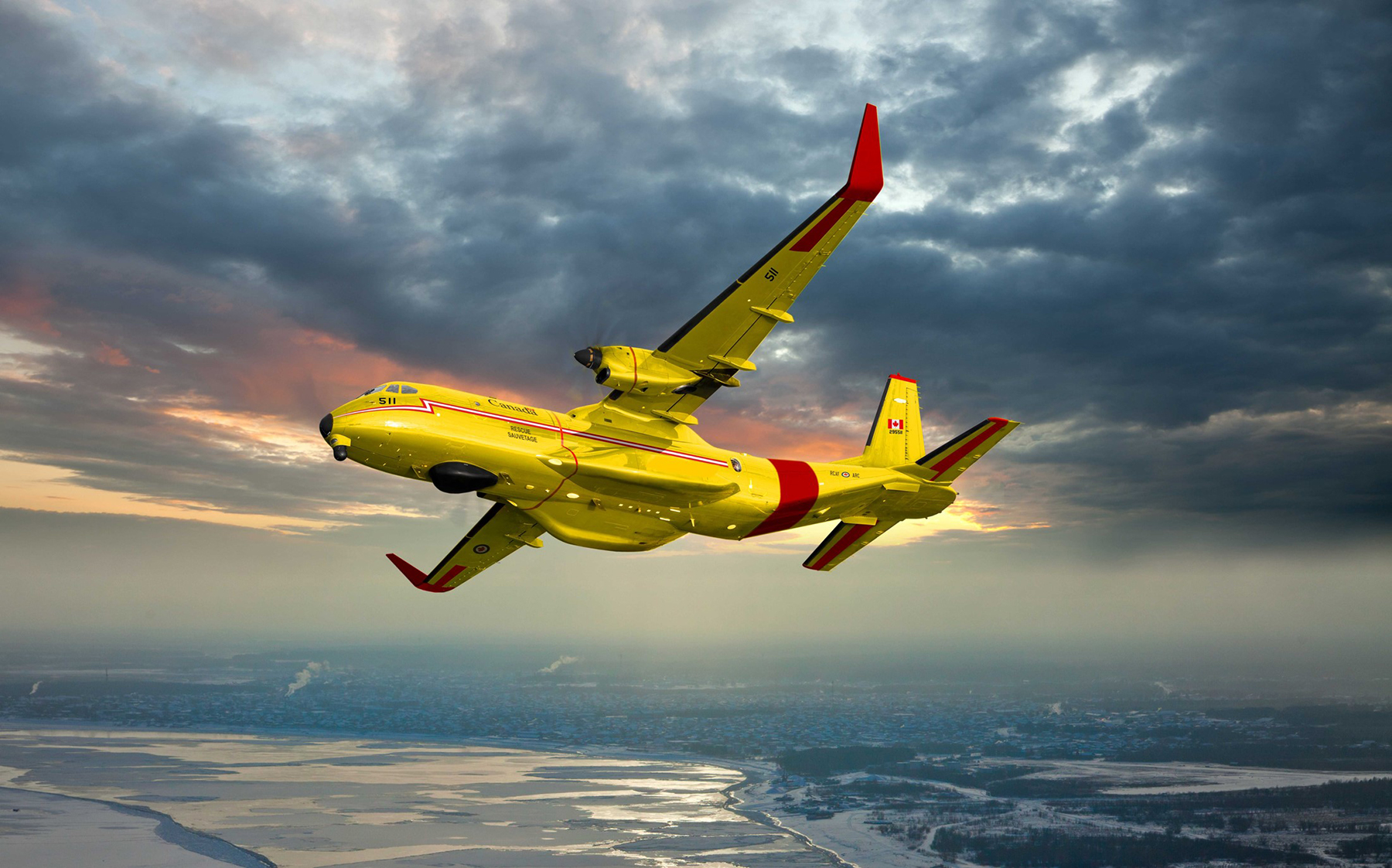 An artist's concept of a yellow aircraft, with red wingtips and markings, flying over a winter landscape