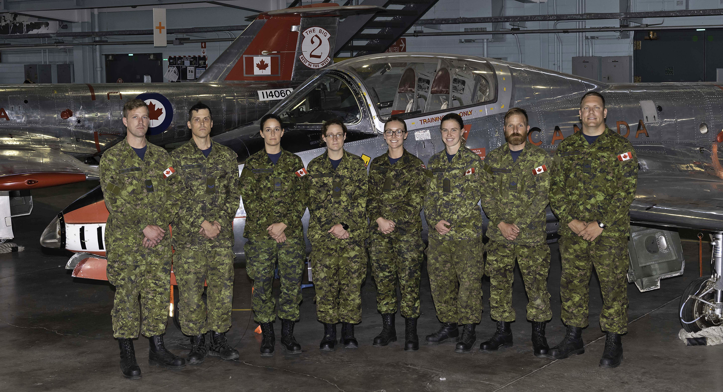 Eight people wearing disruptive pattern military uniforms stand in a row in front of a small aircraft inside a hangar.