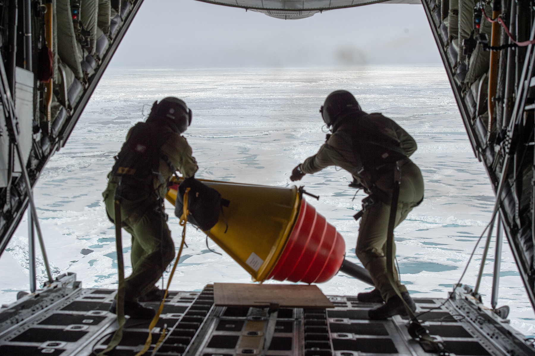Two people wearing olive green flight suits and helmets push a yellow and orange buoy off the ramp of a cargo aircraft flying over ice and snow.