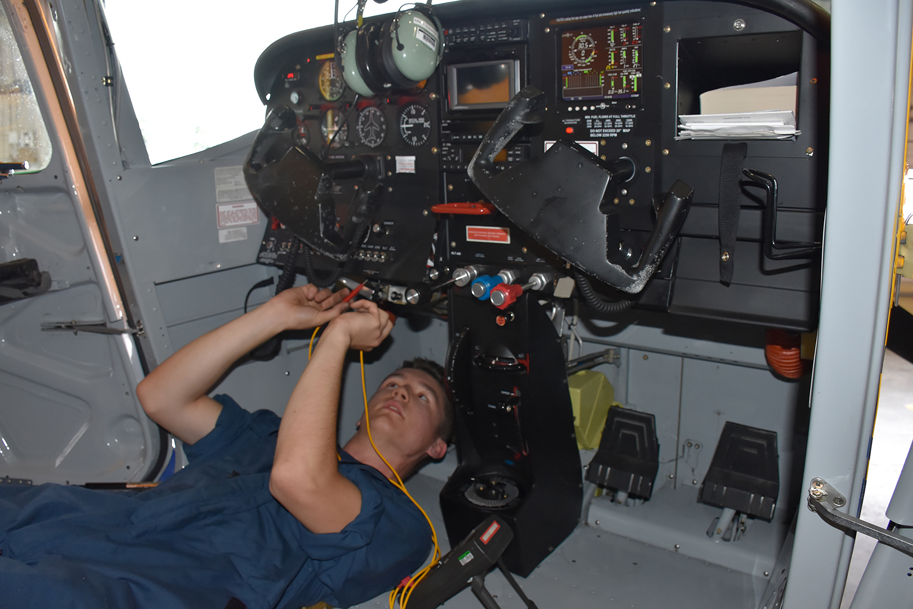 Staff Cadet Mitchell Mansfield tests electrical equipment in the cockpit of a tow plane at Comox Cadet Flying Training Centre, where he is working for the summer as an aircraft maintenance engineer. PHOTO: Captain Angela Sergent