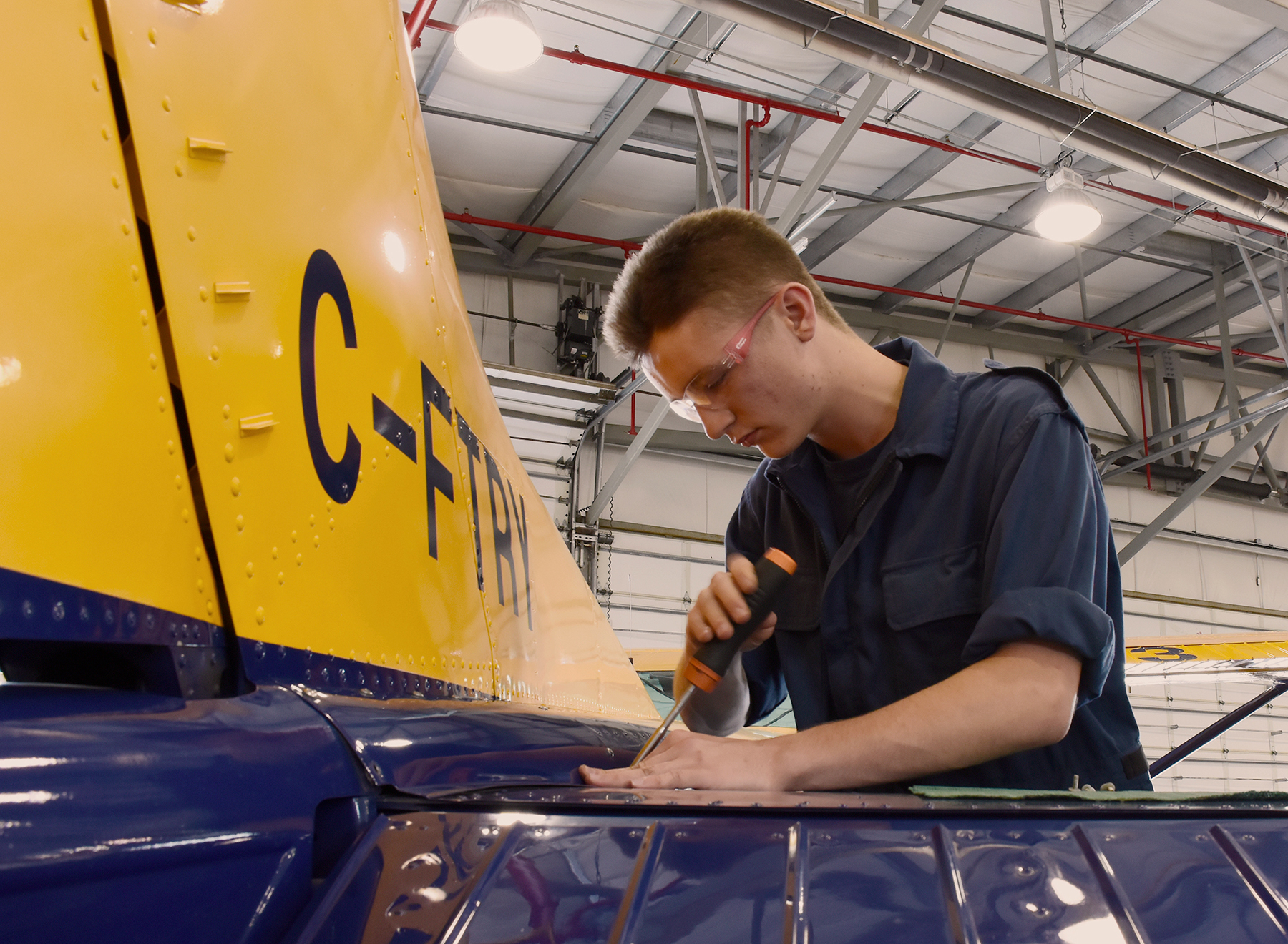 A young man wearing dark blue coveralls works on the tail of an aircraft in a large building.