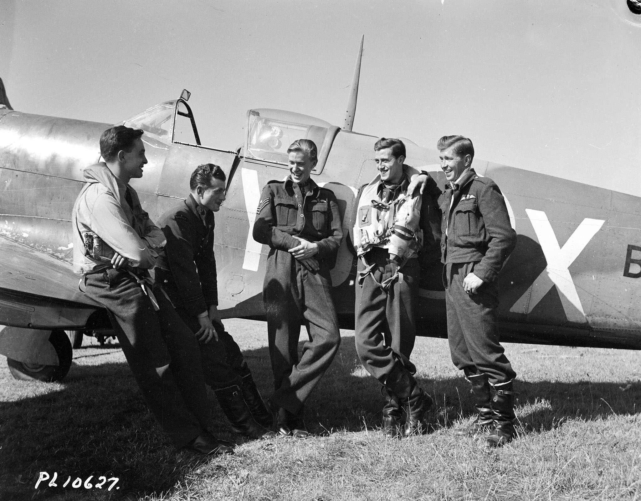 Five men wearing military uniforms stand in front of an aircraft.